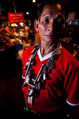 Man met veel Thaise amuletten om zijn nek